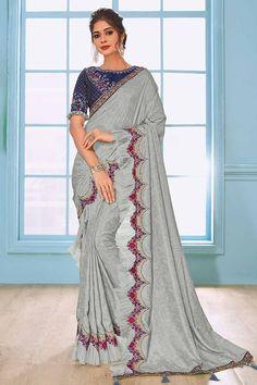 Light Grey raw silk ruffle saree, embellished with zari, stone work, resham work and dori work. It Comes with Sweetheart Neckline, Half Sleeve royal blue banglori silk blouse and matching underskirt