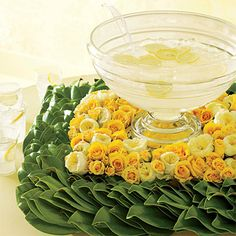 Punchbowl display - green magnolia wreath, then surround the bowl with Aalsmeer gold, flair spray, and garden roses.