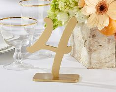 """""""Good As Gold"""" Classic Table Numbers (1-6). These table numbers are as good as gold! Ourclassic Good as Gold Classic Table Numbers (1-6) just beg to be paired with an eye-catching table centerpiece. Add glam mercury glass votives and a mason jar bursting with bright posies for a stunning ambiance your guests won't forget. Ideal for a wedding, this unique decor item couples elegance with a chic attention to detail. Features and facts:  Elegantly designed wood fiberboard table number..."""