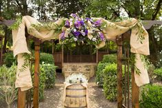 Burlap and flowers ceremony arch | Purple Infused Country Wedding At The Inn at Kelly | Photograph by Callie Hardman Photography  http://storyboardwedding.com/purple-country-wedding-inn-at-kellys-ford/