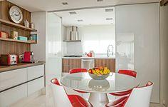Para levar a luz natural que entra pela cozinha até a copa, a designer de interiores Cristina Barbara removeu a parede e colocou, no lugar, painéis de vidro serigrafado. O material é fácil de limpar e a cor branca acinzentada não barra a luminosidade