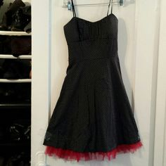 Party dress Pretty black dress with small white polka dots. Spaghetti straps are adjustable.  Crinoline red ruffles at hemline. Zips in back. Missing belt. Can't find it anywhere.  Reflects in price. Great condition Ruby Rox Dresses