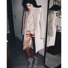 Kylie Jenner wears a Helmut Lang Glossy Leather Shearling Coat over a beige sweater, silk trousers, and gray suede pointed-toe booties