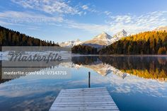 Jetty at Lake Staz with Larch Trees and Snow Covered Piz Nair Reflected in it in Autumn, Canton of Graubunden, Switzerland  – Bild © F. Lukasseck / Masterfile.com: Kreative Stock-Fotografie, Vektoren und Illustrationen für Internet-, Print- und Mobile-Nutzung