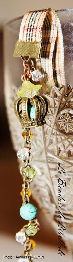 """Bracelet """"Save the Queen""""    Description de l'article  Bracelet composée d'une bande de tissu style burberry et d'une chaîne bronze. Un fil élastique sur lequel est fixé des perles en cristal et des pierre semi-précieuse (Howlite)est tressé entre les maillons de la chaîne.   A la jonction de la chaîne et du tissu se trouve une breloque bronze en forme de couronne.   Un autre cristal est fixé au bout de la chaînette d'extension    Taille/Mensurations/Poids  17cm/20cm reglable avec chaîne…"""
