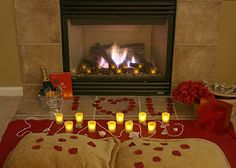 Valentine's day romantic indoor picnic with fireplace rose petals spelling out I Love You, champagne, I heart you candles, and pillows.