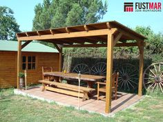 Pergola de madera de abeto laminado lasurado en color nogal, con techo de madera machiembrada y acabada con tegola americana. www.fustmar.com