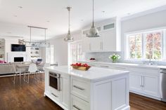 This kitchen renovation stole square footage from an oversized powder room, resulting in a bright, airy space that opens to the dining room and family room beyond. The homeowner loves to cook, so the large island, with its sleek white countertop and ample storage, was a coveted addition.