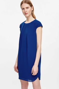 This dress is made from a fluid material with soft neckline pleats at the front and an inverted pleat at the back. An A-line shape, it has neat cap sleeves, a slightly graduated hemline and a hidden zip-up.