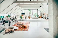 Attic space as living room. All the white is contrasted with few colourful furnishings