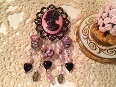 This Handmade Skull Brooch/Pin is made of high end beads and stones,     consisting of:     Handmade Artisan Lampwork Beads,    Handmade Black and Pink Cabachon Lady Skull Cameo Pendant,     Large and Small Swarovski Crystal Accent Beads,    Black Onyx Heart Beads,     Hematite Accents,     Freshwater Pearls,    Large Vintage Look Frame.     This is a substancial brooch or pendant, at least 4 inches in length...$25.