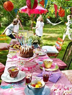 Geburtstagstisch im Garten, im Hintergrund spielende Kinder