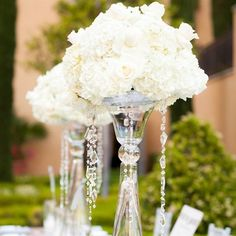 White Floral Centerpieces high glass vases with crystals hanging from the flowers. The floral arrangements were made up of white roses and hydrangeas. #Wedding