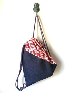 SPRING RED & BLUE  Mochila de lazo, hecha con tela estampada y tela vaquera. Por dentro tiene un forro de tela clara, natural.  La tela vaquera que es bastante gruesa, hace que la mochila s…