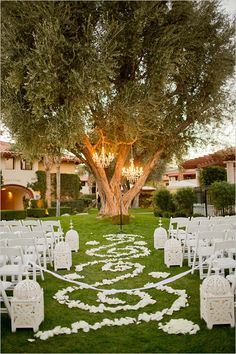 This is lovely ceremony decor, chandeliers hanging from the tree, white lanterns down the aisle.