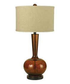 Elegantly designed by Candice Olsen, this beautiful lamp adds exquisite lighting to any living space. Crafted from amber glass with a linen shade, it's a sophisticated piece that's guaranteed to illuminate existing décor. Note: This one-of-a-kind item is made with a unique treatment and may appear in colors and shades different than shown.