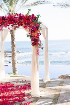 Beach wedding ideas- Beach ceremony drenched in flowers