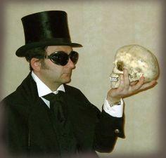 Top hat, Gothic coat, goggles, wing collar shirt, black velvet waistcoat and…