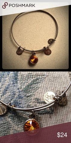🎉HP! 4/2🎉  Alex & Ani Beautiful and sparkly! Orange citrine colored gemstone. (Not my birthstone just one of my favorite colors!) so could be worn with and for everything 😊. Gold metal, smaller charms dangling, great worn condition! Minor scratches and regular wear , slight tarnish on one side still great shape. Adjustable one size fits all bracelet. Alex & Ani Jewelry Bracelets