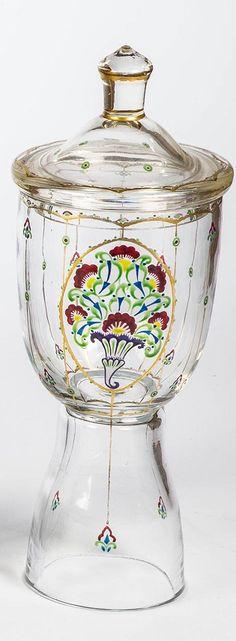 Deckelpokal Farbloses, teils seidenmatt geätztes Glas mit Gold und buntem Transparentemail. Stilisierter Dekor: Medaillon mit Füllhorn und Blumen. H. 26,5 cm Fachschule Haida (Entwurf), um 1915/20