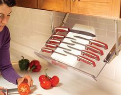 Pull-down racks give you instant access to kitchen essentials without the clutter of spice racks or knife holders. When the cooking is done, the rack swings up against the underside of the cabinet. This is a great way to get rid of the knife rack and keep it safe for children too! #organization #safety #kitchen