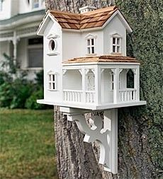 adorable little white two story bird house with cedar shake roof