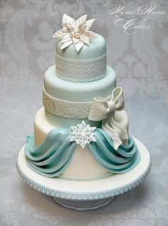 Ivory and pale teal tiered wedding cake with draping, lace, bow, and flower.