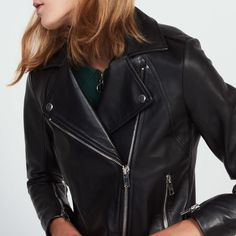 Sandro Biker-style, wraparound jacket in supple lambskin with decorative metal snap buttons, silver zips on pockets and bottom of the sleeves. The model is wearing a size 1.