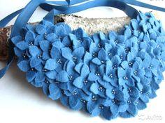 Необычный синий цвет, приглушенный, джинсовый будет особенно хорош в сочетании с белым. Колье выполнено из испанского полушерстяного фетра.Каждый цветочек вырезан вручную, лепестки закреплены между собой и декорированы стеклянным бисером. Яркое, оригинальное и романтичное колье с цветами оценят поклонницы стиля casual. Колье будет хорошо смотреться на открытом вырезе, под светлую рубашку и с водолазкой. Размер колье 20 см на 9 см. Длина атласной ленты колье 60 см.