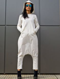 Elegant Harem White Women Hooded Jumpsuit / Romper made of 100% cotton with pockets which you can wear it like a dress. The model has zip bottom of the crotch and when you open the zipper you have Extravagant dress. It is made of high quality natural fabrics / material, soft and breathy, so loose the jumpsuit to make you comfortable all the time. ~~~~I create and made this Unique Jumpsuit with all my love! I think that every women should have her own style and I offer you stylish…