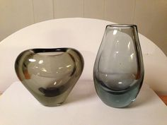 2 Holmegård-vaser. Hjertevase, 8 cm, røgfarvet, 1960. Flad aqua dråbeformet vase u. år, 12 cm. 175 kr. Forum, december 2013.