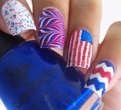 Play with different designs using red, blue and white: the colors of the US flag. There are little glitters on white nail, marbled design, rhinestones formed like the flag and red, blue and white Chevron pattern.