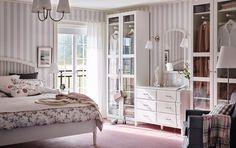 Tradiční ložnice s šedobíle pruhovanou tapetou, růžovou podlahou a bílými šatními skříněmi