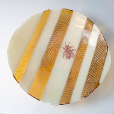 Freeform bowls are made up of varying width strips of screen printed and plain glass layered under varying width strips of clear glass, then fused in a kiln to about 1400 degrees. Bowls are then cold