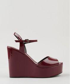 Sandália plataforma feminina desenvolvida em verniz. O modelo tem fechamento por fivela de ajuste.  Altura do Salto: 12cm