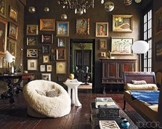 living room of decorator gwynn griffith in san antonio, texas, featuring a john dickinson plaster table, wicker tub chair covered with a shearling throw, french chandelier, and spanish cabinet, flos floor lamp, and original pine flooring