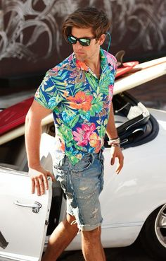 Consider pairing a blue floral short sleeve shirt with blue denim shorts for a trendy and easy going look.   Shop this look on Lookastic: https://lookastic.com/men/looks/blue-short-sleeve-shirt-blue-shorts-green-sunglasses-gold-bracelet/11611   — Green Sunglasses  — Blue Denim Shorts  — Gold Bracelet  — Blue Floral Short Sleeve Shirt