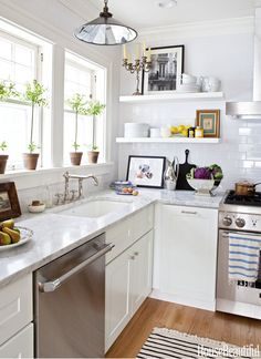 The fresh white kitchen is outfitted with a Thermador dishwasher and range.