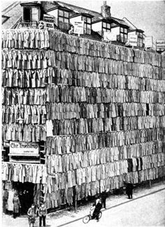This undated photo from an unattributed newspaper shows the facade of a Danish clothier that advertised its overstock coats by covering the building from top to bottom with over a thousand coats. The display was so successful the police had to come and clear the crowd, but the merchant still cleared out his overstock. [ from boingboing ]