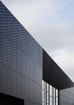 Ystad Arena, Sweden. Between the structure and the façade; mounted in the space between concrete and aluminium, a giant panel of computer-controlled LED lighting brings a dynamic component to the building's expression. The space between the structure and the facade also allows for deeply recessed windows—an elegant and aesthetically appealing solution that also fills the building with reflected daylight. Photo by Åke Eson Lindman Building Skin, Scandinavian Architecture, Architecture Company, Henning Larsen, Architectural Photographers, Factory Design, Interesting Buildings, Famous Architects, Facade Design