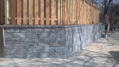 This durable stone #retaining #wall is perfectly accented with a wooden fence. Repin if you agree. | Northern Virginia | Drainage & Erosion Solutions