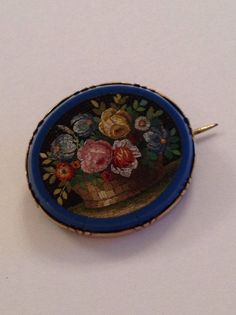 FINEST QUALITY VICTORIAN MICROMOSAIC BASKET OF FLOWERS BROOCH - CIRCA 1850. THE QUALITY OF THE MICROMOSAIC IS SIMPLY BREATHTAKING. DELIGHTFUL BASKET OF FLOWERS JUST LIKE AN OIL PAINTING. MOUNTED IN GOLD. THE SURROUND HAS A COUPLE OF CRACKS AND A PIECE OF CARD HAS BEEN GLUED TO THE BACK POSSIBLY DUE TO CRACKING BUT REMARKABLY THE MOSAIC IS SUPERB CONDITION AND QUALITY. UNMARKED - GUARANTEED 9ct GOLD. ORIGINAL PIN BROOCH FITTING. DIMENSIONS - 2.6 cms x 2.2 cms.   eBay!