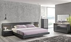 En mi habitación, hay un cama grande y paredes gris.