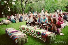 Instead of chairs, throw brightly-colored blankets and quilts over bales of hay.