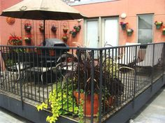 Roof top garden with hanging flower pots on wrought iron and a wall using hangapot.com hangers n Chicago.  Great use of angles and colorful pots.