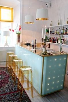 chic home bar: the translucent bar with lighting, the translucent gold bar stools the simple pendant lights with gold interior are all great!