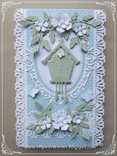 handmade card from Elly's Card Corner ... luv Elly's romantic cards with layers and layers of delicate die cuts arranged in bouquets and adornments  ... sweet  little cuckoo clock die cut and flowers and foliage and edge cuts and ... awesome!!! WOW!!