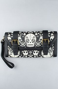 """Faux pebbled leather clutch with skull detail; snap closure with decorative buckle detail; brass hardware; zip pocket and logo plaque on reverse; expandable interior with dual money pockets; two pouches divided by a large center pocket with zip closure; card slots; I.D. slot; fabric lining.  Measures 11""""W x 6""""H x 1.75''D  By Loungefly"""