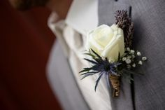 Groom wearing a boutonniere with a white rose and lavender