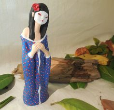 Statuetta raffigurante una geisha, interamente realizzata, lavorata e decorata a mano e cotta in forno per ceramica, successivamente alla cottura è stata decorata con colori acrilici. Indossa un colorato kimono blu a motivi floreali.  Le dimensioni sono 20 cm (7,8) di altezza x 6 cm (2,3) di larghezza  Dalla nostra passione nascono lavori fatti col cuore.....  Il nostro shop per vedere altre creazioni https://www.etsy.com/it/shop/RobArtCreazioni?ref=hdr_shop_menu